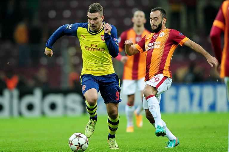 wpid-arsenals-lucas-podolski-l-stroms-past-galatasarays-olcan-adin-during-their-uefa-champions-league-group-d-match-at-tt-arena-stadium-on-december-9-2014-in-istanbul.jpg