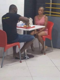 girl looks at man eating alone